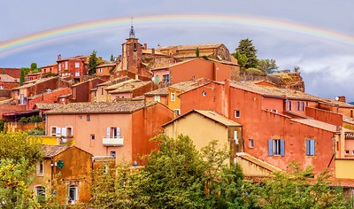 A colorful scene from the French village of Rousillon in Provence, where buildings are made from locally mined ochre pigment. A rainbow in the sky adds to the color.