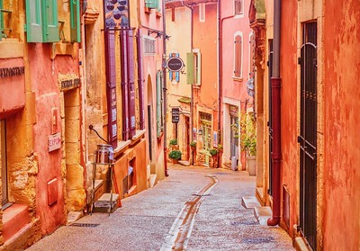 A narrow street in the beautiful French village of Roussillon, where the buildings are made of locally mined ochre and it is said that there are 17 different shades of color.