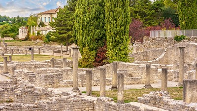 Ancient Roman ruins are situated in the center of the French town of Vaison-la-romaine, surrounded by modern buildings, and are now a tourist site for visitors exploring Provence.