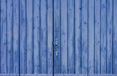 A rustic old barn door, painted lavender blue, in Provence, France.