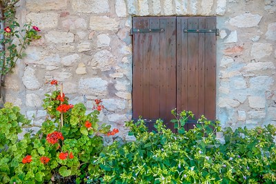 Closed wooden window shutters on the stone wall of an old French farmhouse in a rural village in Provence, France.