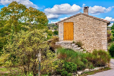 Street view of a quaint, old stone farmhouse in the small, rural village of Buoux in the picturesque Luberon region of Provence, France, in autumn.