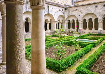 The central courtyard of the 12th century Senanque Abbey, with its Romanesque architecture and manicured gardens.