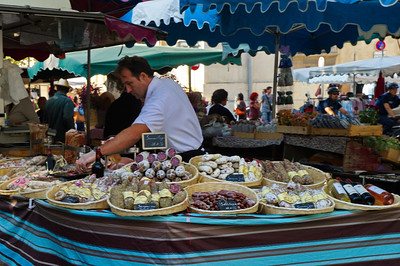 This merchant is selling cured meat, sausage (saucisson in French).  He was slicing off samples to offer customers. yum.