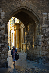 "An elderly lady walks through the gates of the old ""Town Hall"" dating from 1510. (That's old.)"