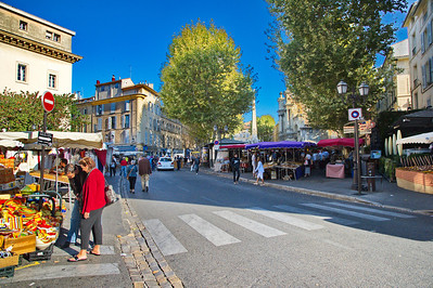 "Every possible space down the street and across the other squares were filled with merchants. The couple on the left are trying to decide which ""Provence"" pottery to buy."