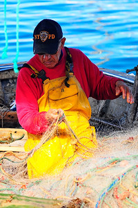 Marseille, France Fisherman repairing his net