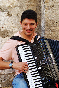 Vence, Adrian plays the accordion on Saturdays to make some extra money.
