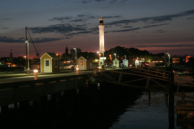 McMillan Wharf, trap sheds, late evening, the UU steeple lit up on the left, town hall in the center and the Provincetown Monument dominating the skyline.