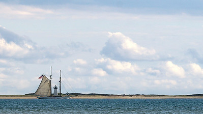 The Spirit of Massachusetts captured at the exact moment it sails past the Long Point Lighthouse in Provincetwon, MA.