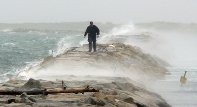 A coast guardsman walking on the breakwater at the end of Commercial Street during a full blown nor'easter.