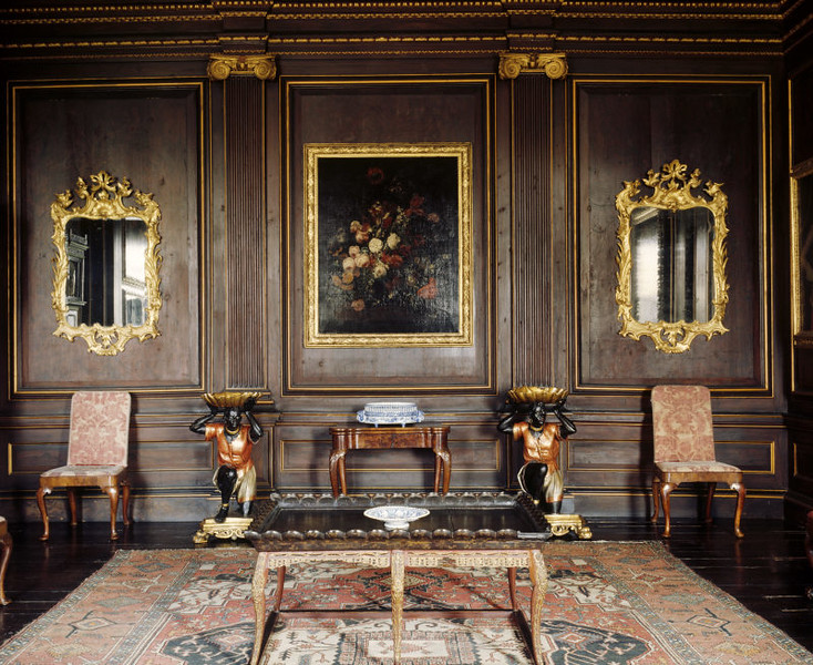 The interior of the Balcony Room. On the panelling hangs two gilt mirrors either side of a Dutch painting, AN ARRANGEMENT OF FLOWERS ON A STONE LEDGE with the signed monogram PHK.