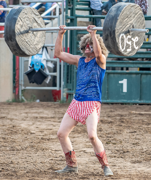 Rodeo clown Sam Lively entertains the crowd by lifting a fake barbell weight during the Weber County Unfair Rodeo, At the Golden Spike Arena in Ogden, on August 5, 2020.