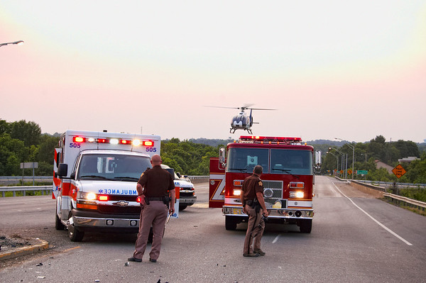 Sheriff's department employees watch from behind ambulance and Glasgow Fire Department's firetruck as the helicopter arrives to transport the injured.