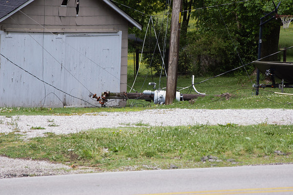 Twisted power lines hang among a fallen utility pole after Saturday' storms. The power lines stretched across the road on highway 90 (Burkesville Road)  at the intersection of Lick Branch Road for most of the morning commute.