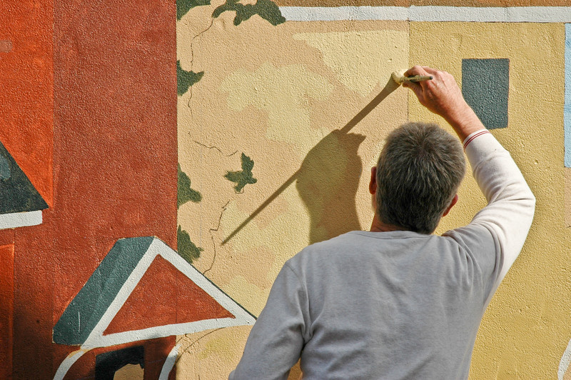 Artist painting mural on wall of Elk's building adjacent to Riverside Gardens Park in Red Bank, New Jersey