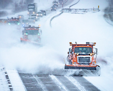 As the snow abates, an echelon formation of three plows clears I-35. I-35 Southbound lane looking north at 195th St; Lakeville