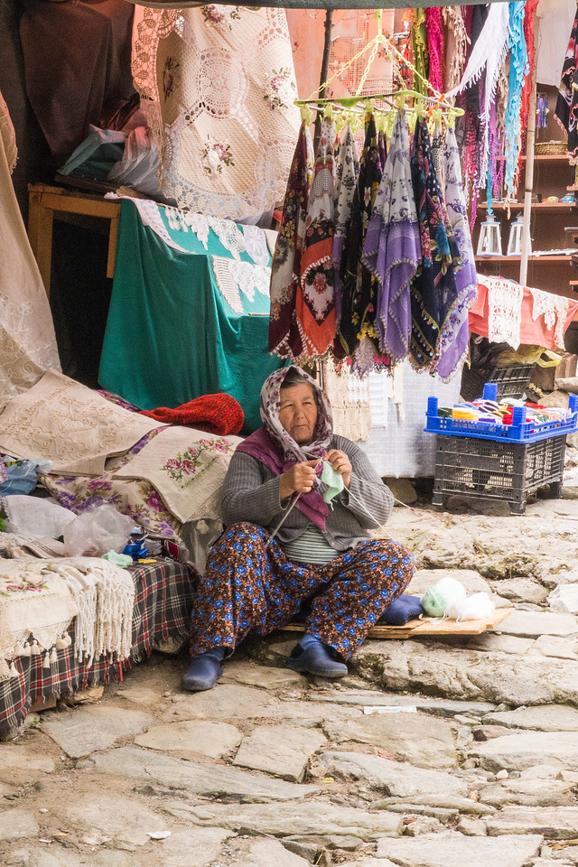Elderly woman knitting in front of her shop in Şirince