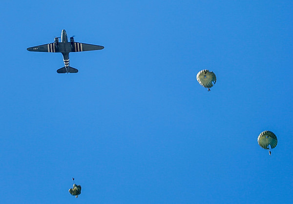 A C-47 / C-53 over the drop zone with jumpers under canopy.