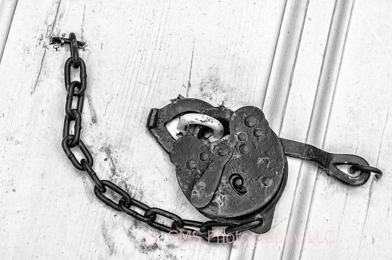 An old padlock secured by chain and hooked at both ends to white doors.
