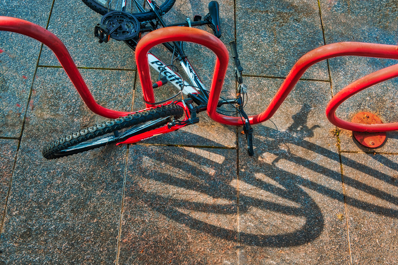 Bicycle In Stand Resting With Shadows