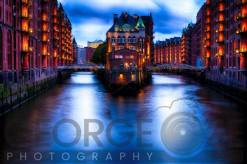 Water Castle on an Island Between Warehouse Buildings Illuminated at Night, Hamburg, Germany