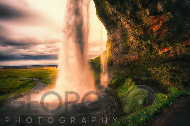 View of the Seljalandsfoss Waterfall Behind from a Cave at Sunset, Iceland