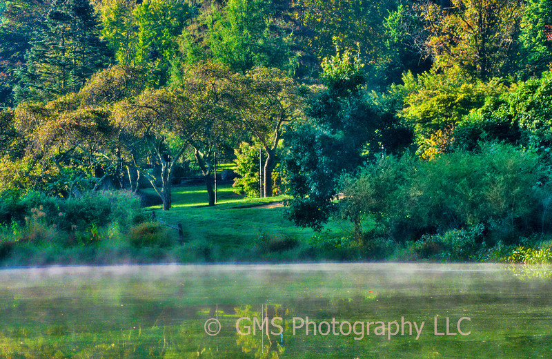 Early autumn morning mist rises from lake at Holmdel Park, Holmdel, New Jersey