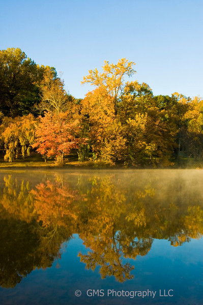Reflection of autumn tree colors in lake with mist on surface of water in Holmdel Park in Holmdel New Jersey