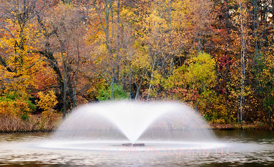 Fountain in the pond at Veterans Park in Hazlet, New Jersey with autumn leaves in background