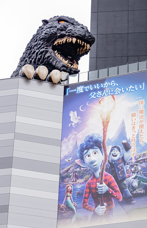 Godzilla looms above latest Disney hero at movie theater.  Shinjuku