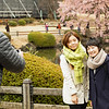 Andy assists visotirs capture an image with cherry blossoms.  Shinjuku Gyoen National Garden