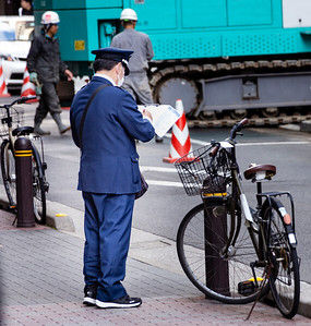 Parking police ticketing bicycle; Ginza Shopping District