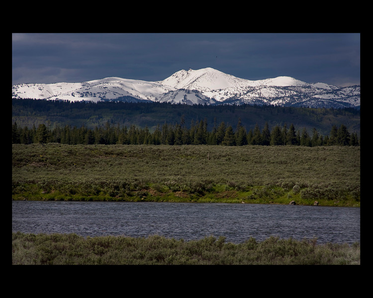 Madison River and snow covered mountains near Yellowstone National Park.