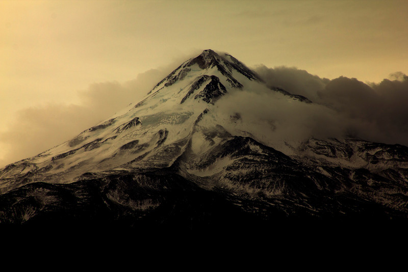 Mountain peak of volcanic Mount Shasta in Northern California in October clouds. 2010.