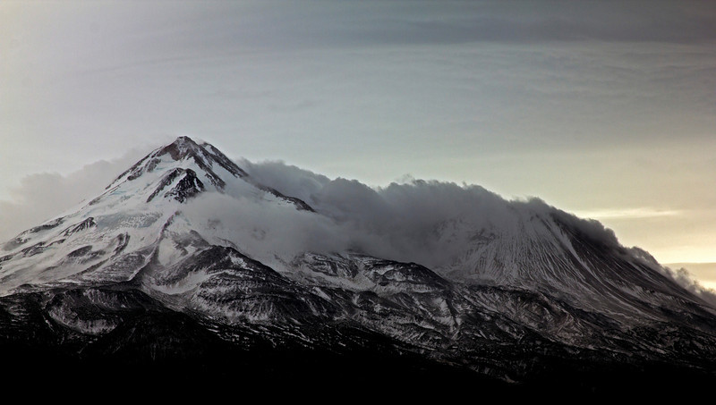 Mount Shasta in Northern California enshrouded with clouds on a cloudy day in October after snows the night before. Oct 2010.
