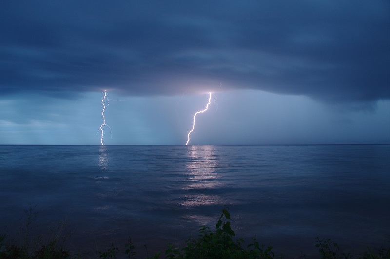 Lightning strikes over lake superior from Michigan coastline.