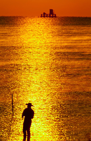 Sunrise over the Gulf of Mexico at Aransas National Wildlife Refuge and fisherman with oil platform in the background. Texas, 2007.