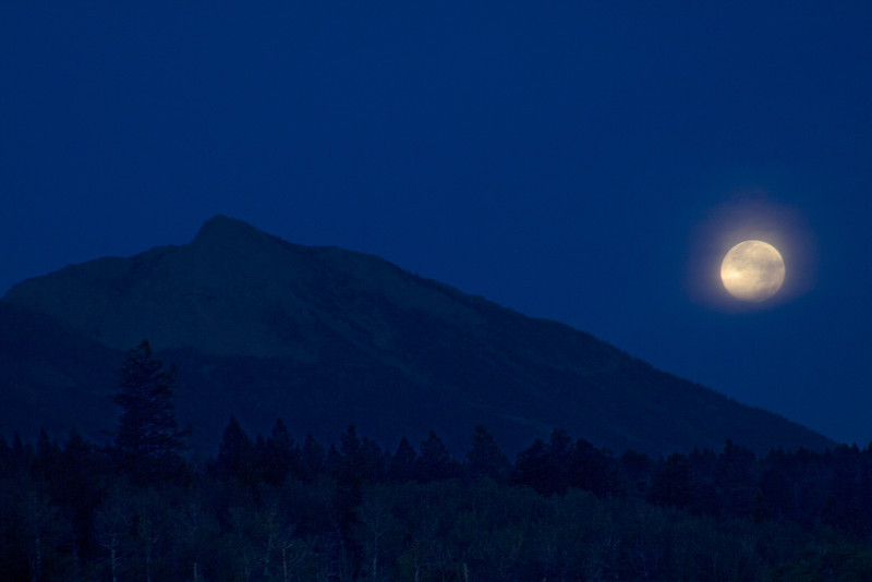 Blue moon setting over Mt. Nemesis on Aug 31 2012. The moon was setting into clouds that made the glow around it. morning. Idaho.