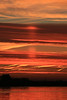 This is an Upper Sun Pillar that is lighting the cloud above the sun, which is still below the horizon. Sacramento River is in the foreground. Dec 14, 2012.  This is made by millions of glistening crystals in the atmosphere.