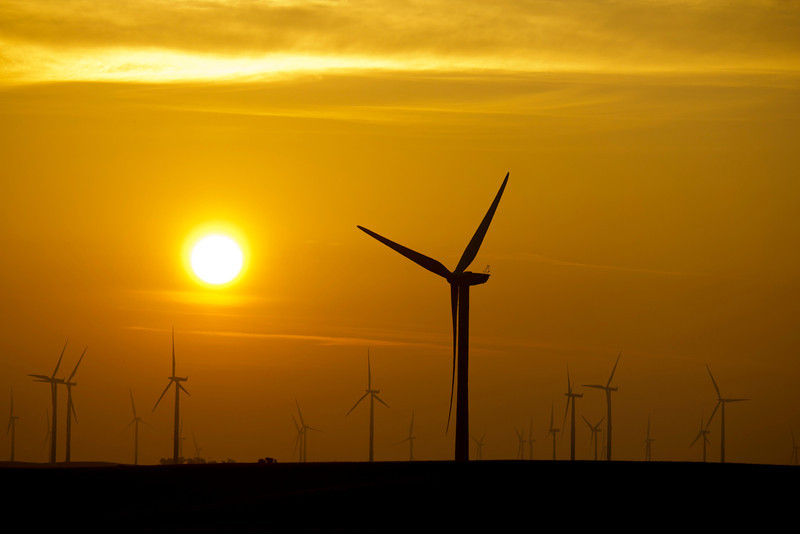 Windmills are silhouetted behind rising sun at Wind farm near Rio Vista, California, December 2011