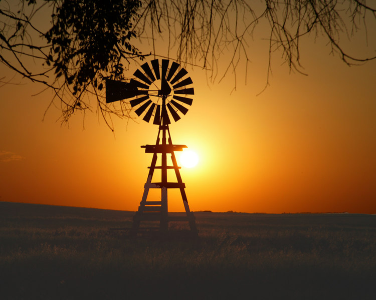 Windmill silhouetted against setting sun in Badlands of South Dakota.