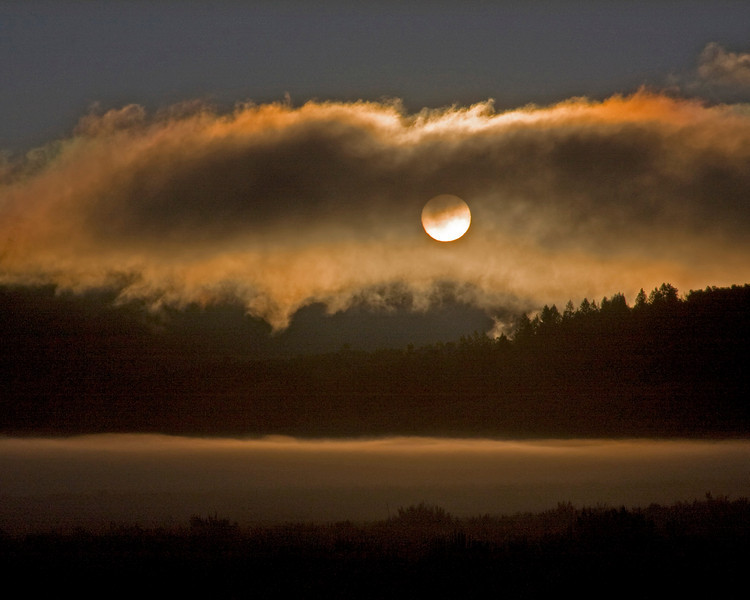 Sun rising through morning fog in Sawtelle Meadows, itself covered in fog, Island Park, Idaho. September 2008.