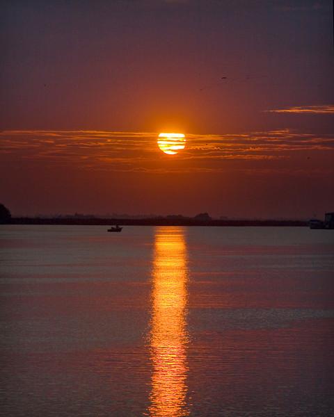 Sun reflected in the waters of the lower Mokelumne River in the Sacramento River Delta region, near Isleton, CA.