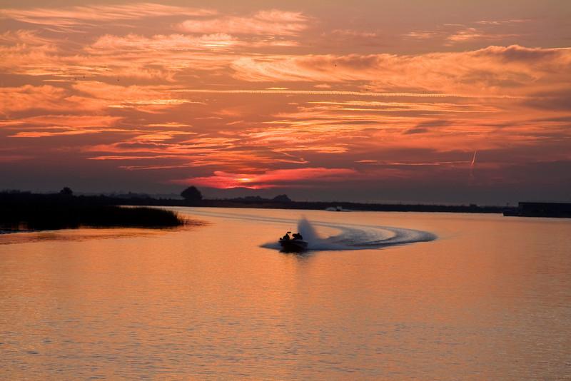 Boat speeding up the lower Mokelumne River at Sunrise in the Sacramento River Delta region, near Isleton, CA.