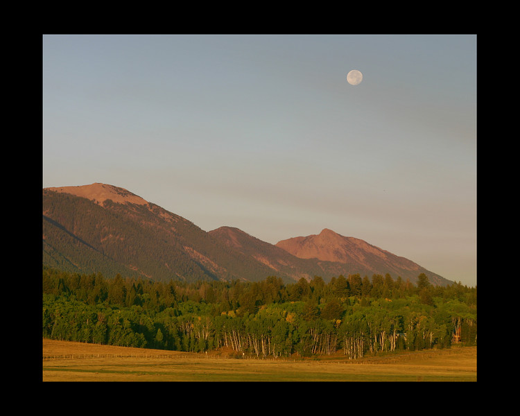 Moonset at sunrise over the East Centennial Mountains of Idaho. August 2007 Smoke from large fires west of here.