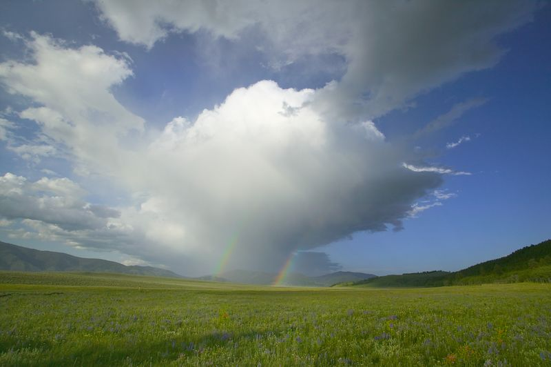 The storm drops two rainbows in the distance over Island Park, Idaho.