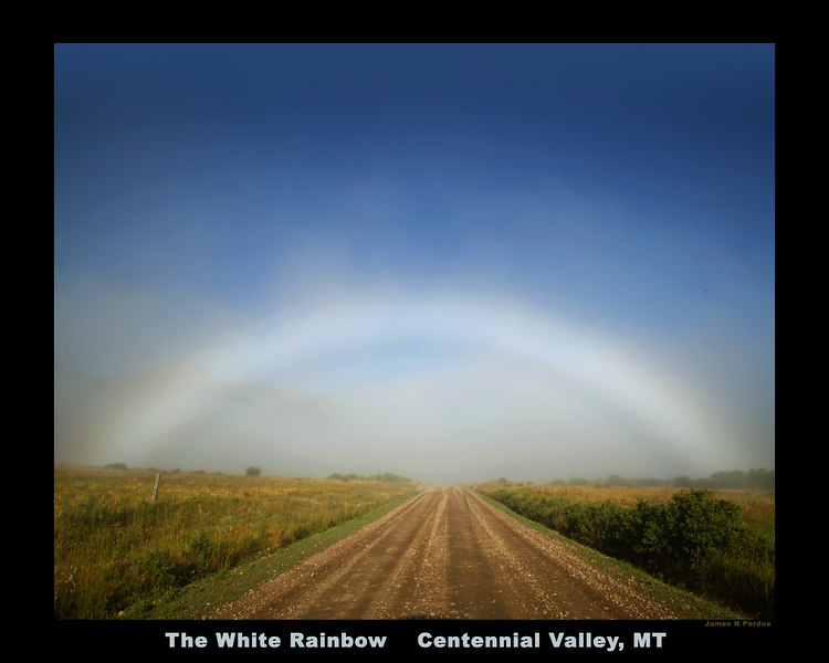 Great example of a White Rainbow, or Fogbow in Centennial Valley, Montana, August 5, 2006. This is caused by sunlight at just the right angle hitting microscopic fog droplets, too small to create a color prism (and thus a real rainbow). It was really impressive walking down this road and see it hang in for a long time.