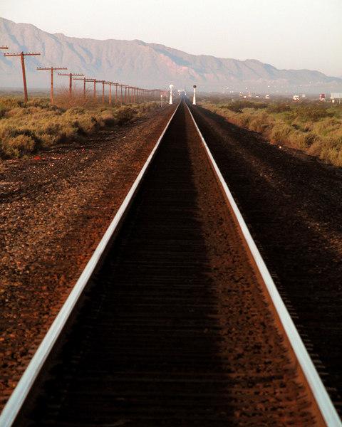 Desert train tracks disappear into the Arizona Mountains near Dateland, AZ, looking West.