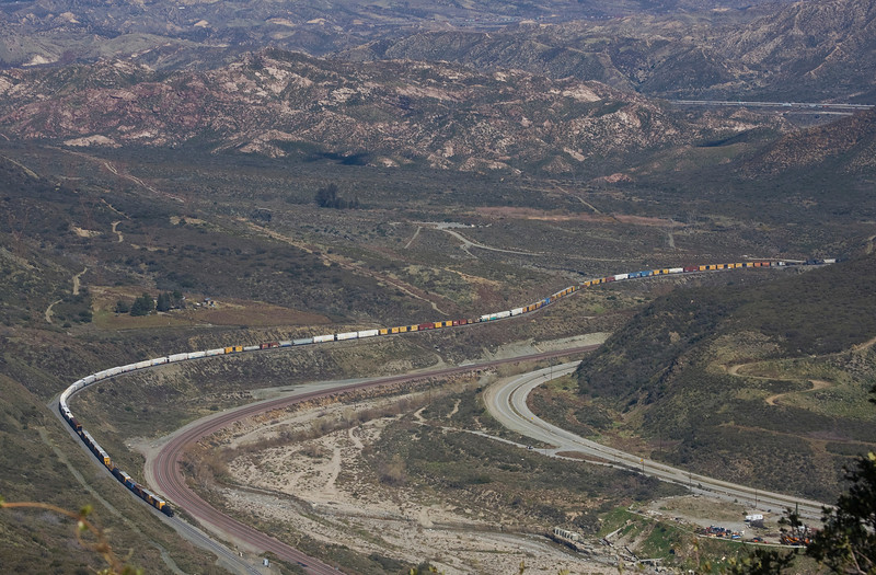 A Long train edging north toward Cajon Pass along Interstate 15 in southern California. February 8, 2010.
